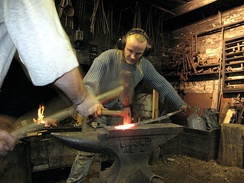 A blacksmith working with a sledgehammer, assistant (striker) and Lokomo anvil in Finland