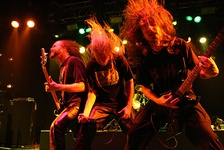Death metal band Asphyx headbanging during a performance.