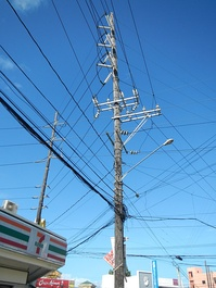A 115 kV subtransmission line in the Philippines, along with 20 kV distribution lines and a street light, all mounted in a wood subtransmission pole