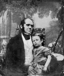 Darwin in his thirties, with his son dressed in a frock sitting on his knee.