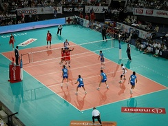 An image from an international match between Italy and Russia in 2005. A Russian player on the left has just served, with three men of his team next to the net moving to their assigned block positions from the starting ones. Two others, in the back-row positions, are preparing for defense. Italy, on the right, has three men in a line, each preparing to pass if the ball reaches him. The setter is waiting for their pass while the middle hitter with no. 10 will jump for a quick hit if the pass is good enough. Alessandro Fei (no. 14) has no passing duties and is preparing for a back-row hit on the right side of the field. Note the two liberos with different color dress. Middle hitters/blockers are commonly substituted by liberos in their back-row positions.