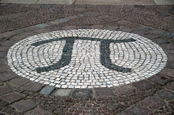 A photograph of the Greek letter pi, created as a large stone mosaic embedded in the ground.