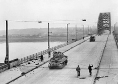 British tanks of XXX Corps cross the road bridge at Nijmegen.