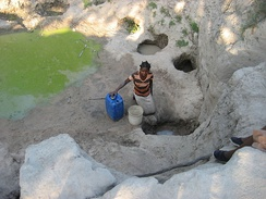 Woman fetching water during the dry season from a polluted source in Machaze District of the Central Manica Province.
