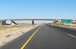 A rural stretch of I-5 in California; two lanes in each direction are separated by a large grassy median and cross-traffic is limited to overpasses and underpasses