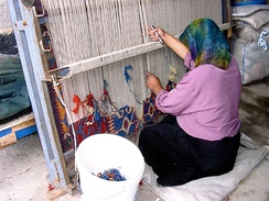 A woman in Konya, Turkey, works at a vertical loom