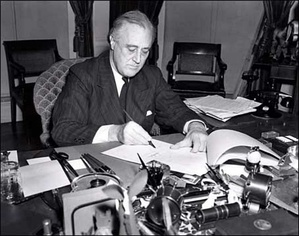 President Franklin Roosevelt signing the Lend-Lease Act, March 11, 1941.