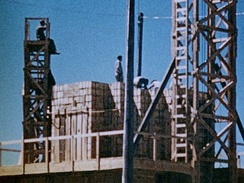 Men stack crates of high explosives for the 100-ton test