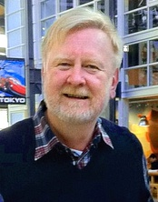 An older man is seen wearing a blue sweatshirt over a collared shirt with a red and blue plaid design.