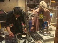 Two hip hop DJs creating new music by mixing tracks; DJ Hypnotize (left) and Baby Cee (right)