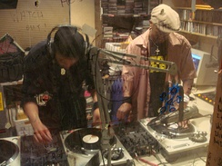 Two hip hop DJs creating new music by mixing tracks from multiple record players. Pictured are DJ Hypnotize (left) and Baby Cee (right).