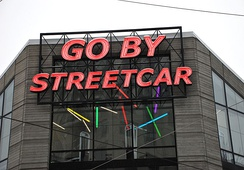 "A sign in Portland that reads ""go by streetcar."" Trams are typically called streetcars in North America."