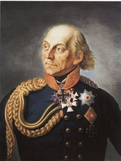 Painting shows a balding man wearing a dark blue military uniform with a gold collar and gold braid on his right shoulder. He wears the Iron Cross and Pour le Mérite awards.