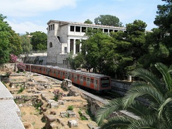 An ISAP train (Green Line) passes by the Stoa of Attalos in central Athens
