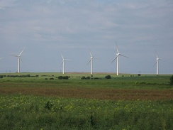 An area of flat green fields with five starkly white wind turbines standing out from the background of a blue sky.