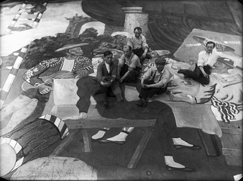 Pablo Picasso (wearing a beret) and scene painters sitting on the front cloth for the ballet Parade