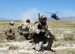 "Pararescuemen and a simulated ""survivor"" watch as an HH-60G Pave Hawk helicopter comes in for a landing."