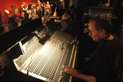 An audio engineer adjusts a mixer while doing live sound for a band.