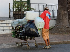 A homeless person collecting recyclable materials in Stellenbosch, South Africa.