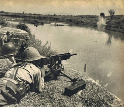 Japanese soldier firing across the Miluo River during the Battle of Changsha