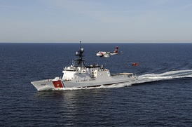 A United States Coast Guard cutter with one of the force's maritime patrol aircraft and a helicopter