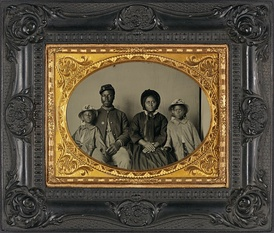 Union soldier in uniform with family; he has been identified as Sgt. Samuel Smith of the 119th USCT[12]