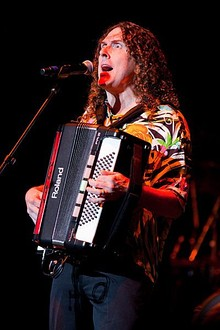 A long-haired man plays an accordion and sings into a microphone.
