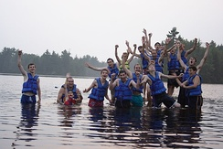 Attendees of summer camps often enjoy outdoor activities. This photo of a YMCA camp shows campers in a lake.
