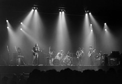 A monochrome image of members of the band. The photograph is taken from a distance, and is bisected horizontally by the forward edge of the stage. Each band member and his equipment is illuminated from above by bright spotlights, also visible. A long-haired man holds a guitar and sings into a microphone on the left of the image. Central, another man is seated behind a large drumkit. Two men on the right of the image hold a saxophone or a bass guitar and appear to be looking in each other's general direction. In the foreground, silhouetted, are the heads of the audience.