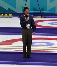 Photograph of Romney standing with microphone in middle of curling lanes