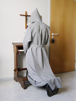 A Trappist novice kneeling at the cross