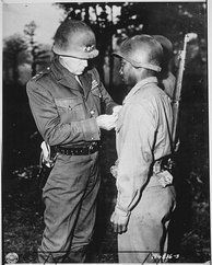 Patton pins a Silver Star Medal on Private Ernest A. Jenkins, a soldier under his command, October 1944