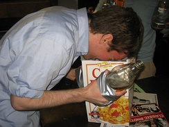 A fraternity member with bottles of malt liquor affixed to each of his hands with duct tape vomits into a box of breakfast cereal.