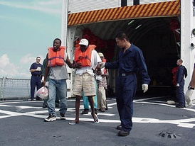 Haitian migrants are escorted off the Coast Guard Cutter Tampa's fantail to an awaiting Haitian Coast Guard vessel during repatriation