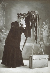 Photographer Jessie Tarbox Beals standing next to her camera