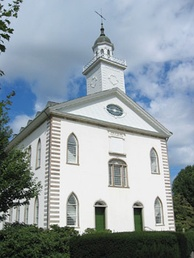 A white two-story building with a steeple