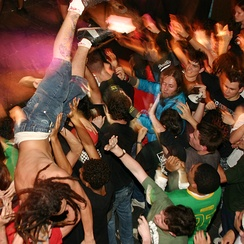 Crowdsurfing over a mosh pit.
