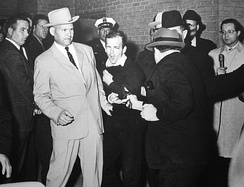 Ruby shooting Oswald, who is being escorted by Dallas police. Det. Jim Leavelle is wearing the tan suit.