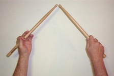 A pair of drumsticks held in traditional grip.