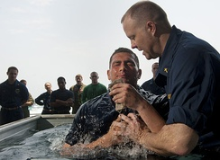 A Baptist chaplain aboard a US navy aircraft carrier baptizes a mate