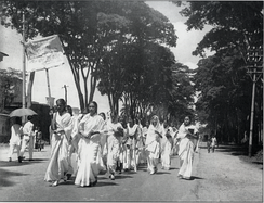 Female students, dressed in white, march down a street.