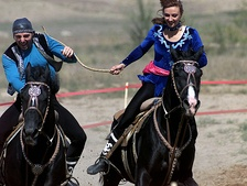 "Horse riders in traditional dress demonstrate Kazakhstan's equestrian culture by playing a kissing game, Kyz Kuu (""Chase the Girl""), one of a number of traditional games played on horseback.[14]"