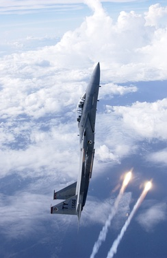 An F-15 Eagle climbing and releasing flares