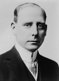 Back and white photograph of a white man wearing a high collared shirt, tie, and dark jacket
