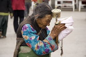 An elderly Tibetan woman with a prayer wheel inscribed with mantras
