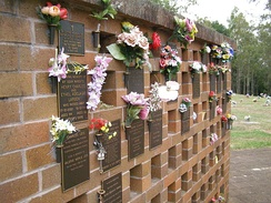 A columbarium wall at Lawnton, Queensland, showing empty niches, plaques and flower holders