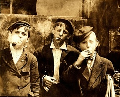 Newsies smoking at Skeeter's Branch, St. Louis, MO. Photograph by Lewis Hine, 1910