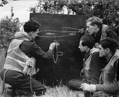An RAF Flight Sergeant instructs fellow-pilots on features of the V-1 flying bomb
