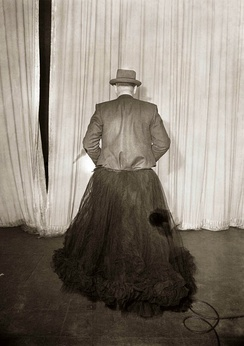 Back view of man (presumably a detective) in a tulle skirt behind a stage curtain. Found in an envelope marked 'Tivoli dressing room fire, 1945'.