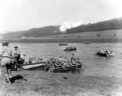 From newly captured town, members of the 16th Infantry Regiment, 1st Infantry Division, cross the Weser River in assault boats to take Furstenberg. 8 April 1945.